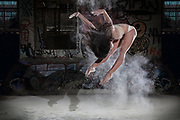 Ballet dancer on pointe dances of a floor covered with powder