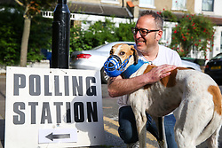 © Licensed to London News Pictures. 23/05/2019. London, UK. A voter arrives at a polling station with his dog in Haringey, north London to cast a vote in the European Parliament elections. Photo credit: Dinendra Haria/LNP