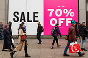 People walk past clothes shop displaying a 70% off sale sign in Oxford Street, London, UK on January 03, 2019