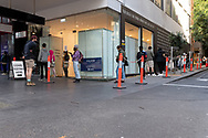 People line up and around the corner outside a COVID-19 testing Clinic on Bourke Street this afternoon in Melbourne after lockdown was extended for another 7 days on the day it enters 6th day of the state wide COVID-19 lockdown that has been placed on the State of Victoria. (Photo by Michael Currie/Speed Media)