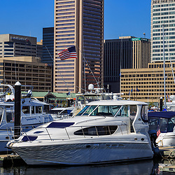Baltimore, MD / US - October 15, 2016: Boats at dock the city's Inner Harbor waterfront accent the cityscape.