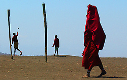 The signs of changing times are evident as Maasai children relax with a game of football as their elders walk by cloaked in traditional clothing during lunch break at the Endulen Primary school in Ngornogoro District in Tanzania September 29, 2003.  Most Maasai now see the value of sending their children to school so they can have a voice in the government to protect themselves with increasing land loss. The Maasai were thrown out of the Crater in 1972 in the name of conservation and are being threatened again  under a torrent of new legislation. Like other indigenous people the world over, they continue to be evicted from their land in the name of tourism and conservation. They have lived on these lands for centuries but now struggle to survive on their borders, especially in the difficult drought years. Though they were able to live in harmony with the wildlife for centuries, the places with rich water sources are now preserved for tourists.  Eco-tourism, the government solution to chronic poverty, brings in vast revenues but sadly, the dispossessed Maasai are not allowed to benefit. Only a handful, mostly foreign owned tourist operators profit and only a tiny portion of the money actually filters through to the local economy.