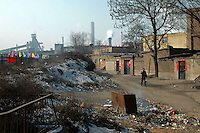 """China, Taiyuan, 2008. A factory worker leaves his home next to """"Tai Gang,"""" Taiyuan Iron and Steel, Shanxi's largest employer and a vital part of China's metal production capacity.."""