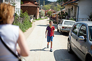 School boy with a soccer shirt walking the street in the city of Crnik, Macedonia.