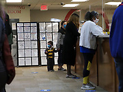 On the first day of early voting, a mother takes her child to vote.