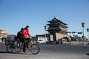 Cyclists ride their bikes past Qianmen in Beijing, China, on Tuesday, Dec. 01, 2015.