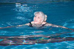 Older woman swimming in the pool at her local leisure centre,