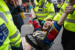 London, UK. 16th April 2019. Police officers arrest a climate protester from Extinction Rebellion at Oxford Circus on the second day of International Rebellion UK activities to call on the Government to take urgent action to address climate change.