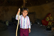 Indian boy in home made of mud bricks and cow dung in Bishnoi tribe village near Rohet in Rajasthan, India