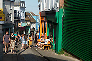People outside a cafe in Folkestone, England, United Kingdom. Folkestone is a port town on the English Channel, in Kent, south-east England. The town lies on the southern edge of the North Downs and was an important harbour and shipping port for most of the 19th and 20th centuries.