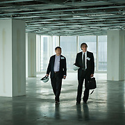 PR Photography for General Electric (GE). Men walking through office tower construction site.