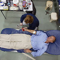 (PFEATURES) Rumson 10/15/2002   Bob lies on the table giving blood as technician Danelle Schork of Eatontown checks on the bag of blood.      Michael J. Treola Staff Photographer.........MJT