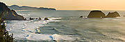 At sunset, the Pacific Ocean breaks waves on Three Arch Rocks and high bluffs at Oceanside, Oregon, USA. Panorama stitched from 3 overlapping images.