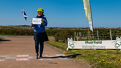 East Lothian, Scotland, United Kingdom, 25th April 2021. Virtual Kilt Walk: Kilt walkers supporting Muirfield Riding Therapy charity cross a 'finish line' to celebrate their participation in their 'Round the World'  fund raising campaign. Each team chose a destination and walked, cycled or rode the miles from home to their chosen point, totalling the 24,900 miles of the earth's circumference and raising over £10,000. Pictured: Corinne Mitchell who walked and rode the 500 miles distance to Inverness and back. Sally Anderson / EdinburghElitemedia.co.uk
