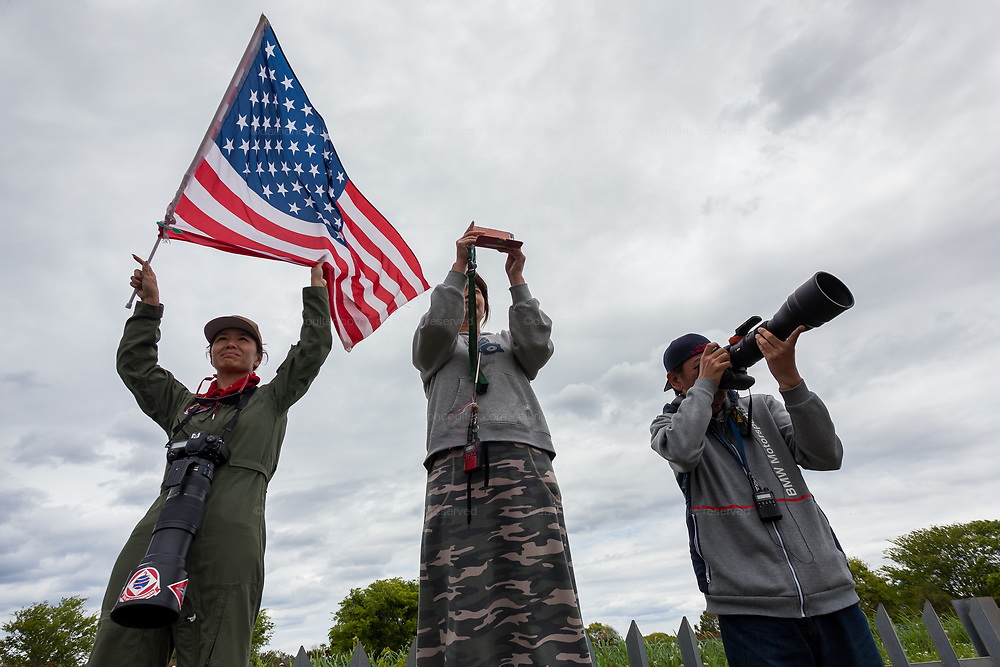 Military aircraft enthusiasts wave an American flag and uses long lenses to look into  Naval Air Facility, Atsugi airbase as F18 fighter jets take off. Yamato, Kanagawa, Japan. Monday April 29th 2019. The F18 of the Royal Aces squadron is a rare visitor to this US and Japan Self Defence Force base in Kanagawa. Once stationed there the jets, which were the cause of lawsuits related to noise levels by local residents, have been moved to Iwakuni airbase. Many aircraft enthusiasts still turn put to watch and photograph them when they visit however..
