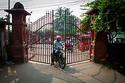 A man on a motorbike wriggles through the locked gates to Curzon Hall at the University of Dhaka, on the 29th of September 2018 in Dhaka, Bangladesh. The campus is regularly used as a cut through avoiding the busy traffic on High Court Street.