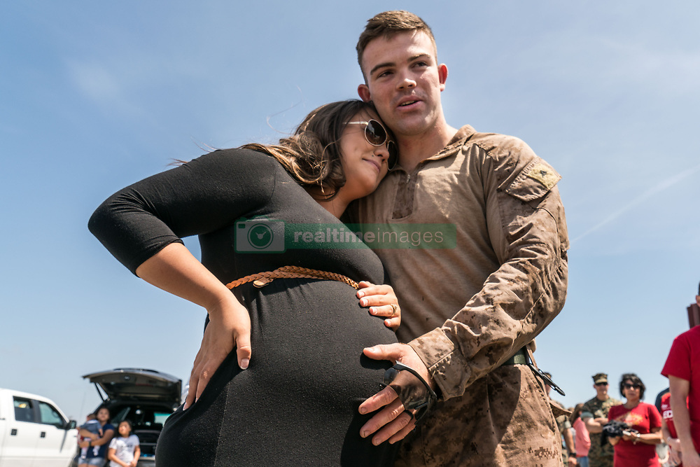 May 11, 2017 - Oceanside, California, U.S. - MADISON MCMAIN, stands with her husband Lance Corporal SHANE MCMAIN, after seeing his pregnant wife for the first time at Camp Pendleton after a 7 month deployment overseas. Marines and sailors from the 11th Marine Expeditionary Unit returned to Camp Pendelton after serving 7 moths in the Western Pacific, Middle East and Horn of Africa. (Credit Image: © Ken Cedeno via ZUMA Wire)