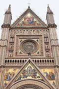 The facade of the Duomo di Orvieto illuminates under a ray of sun on a cloudy day, Orvieto, Umbria, Italy.