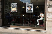 A man eats his own food from a plastic bag in the sunlit window of a central London cafe, on 25th October 2018, in Piccadilly, London, England.