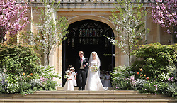 Newlyweds Thomas Kingston and Lady Gabriella Windsor smile on the steps of the chapel after their wedding at St George's Chapel in Windsor Castle.