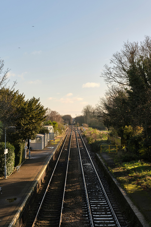 Portrait view down from the footbridge at Trimley Station. Looking towards Felixstowe. The only platform in use can be seen on the left. The track on the right continues to the Port of Felixstowe.<br /> <br /> Photo by Jonathan J Fussell, COPYRIGHT 2020