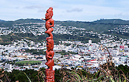 A red Pouwhenua or carved wooden post, against the backdrop of New Zealand's capital city Wellington, viewed from Mt Victoria lookout