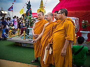 "21 NOVEMBER 2015 - BANGKOK, THAILAND: Buddhist monks pose for a ""selfie"" at the Wat Saket temple fair. Wat Saket is on a man-made hill in the historic section of Bangkok. The temple has golden spire that is 260 feet high which was the highest point in Bangkok for more than 100 years. The temple construction began in the 1800s in the reign of King Rama III and was completed in the reign of King Rama IV. The annual temple fair is held on the 12th lunar month, for nine days around the November full moon. During the fair a red cloth (reminiscent of a monk's robe) is placed around the Golden Mount while the temple grounds hosts Thai traditional theatre, food stalls and traditional shows.     PHOTO BY JACK KURTZ"