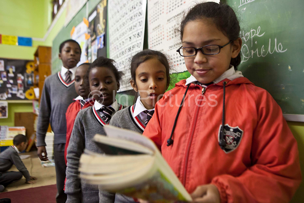 A young school girl reads to her class in a classroom in St Agnes Primary School, Woodstock, Cape Town, South Africa.  Some other children stand next to her in a queue waiting for their turn.  They are standing by the green board at the front of the class.