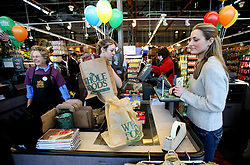 01 Feb 2006. Uptown, New Orleans, Louisiana.  Post Katrina. <br /> The Whole Foods supermarket reopens amidst great celebration 5 months after  the city was hit by Hurricane Katrina. A customer waits at the check out to pay for her goods.<br /> Photo; Charlie Varley/varleypix.com