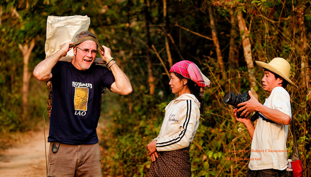 Trading Places: The temporary role reversal between an American photographer, who hoists a heavy load to his forehead and a Yao woman, while a local gentleman fumbles with and almost drops the photographers expensive camera, in Muang Sing, Laos.