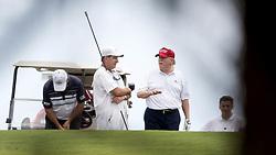 April 8, 2017 - West Palm Beach, Florida, U.S. - President Donald Trump talks to a caddie during a round of golf at Trump International Golf Club in West Palm Beach, Florida on April 8, 2017. (Credit Image: © Allen Eyestone/The Palm Beach Post via ZUMA Wire)
