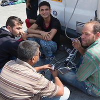 Illegal migrants charge their phones at the power outlets offered by a TV broadcast van in front of the main railway station Keleti in Budapest, Hungary on September 03, 2015. ATTILA VOLGYI