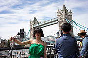 Asian tourist taking a selfie using her selfie stick at Tower Bridge in London, United Kingdom.