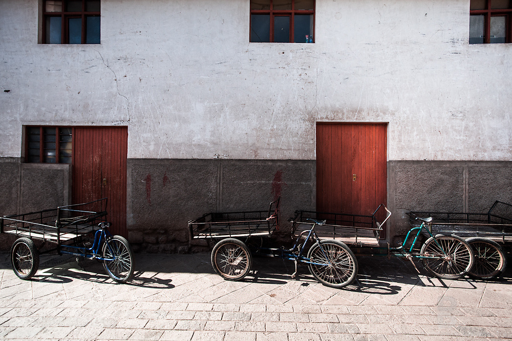 Four bike carts, which are heavily used throught peru to transfer numerous types of food and goods from markets and stores and homes, sit parked against a adobe and cement store in Pisac, Peru.