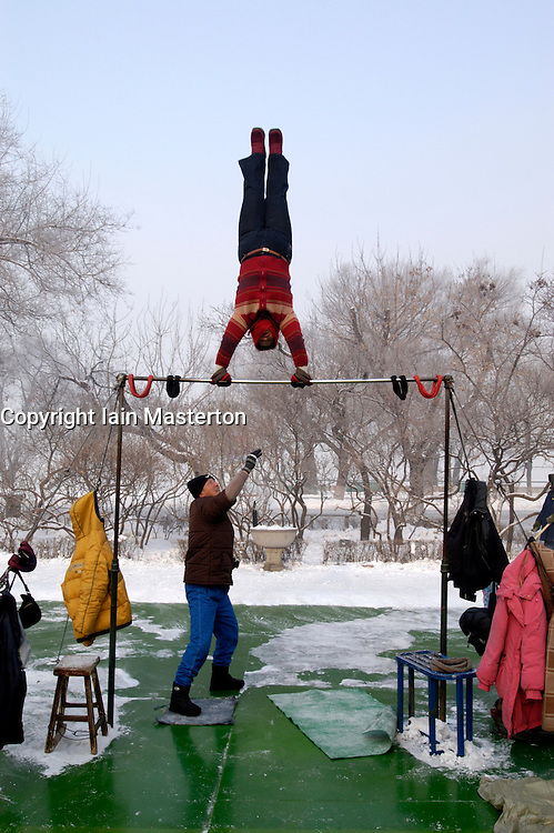 Elderly woman doing gymnastics in early morning in Stalin Park Harbin during winter
