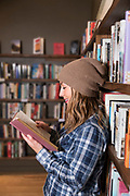 Portrait of a young woman reading a book in a bookstore.