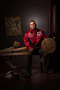 John Dennis, storyteller and Cultural Director for the Aroostook Band of Micmacs, photographed at the Micmac Cultural Center, Presque Isle. Mr. Dennis is holding an eagle feather and a drum he uses in storytelling. He is seated on an antique splint-shaving bench, and on the floor beside him are traditional games used in educational programs.
