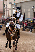 A masked rider participating in the Sa Sartiglia festival tries to pierce a suspended star with a sword at full gallop on horseback, during the Stella competiton, Oristano, Sardinai, Italy