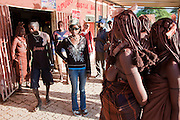 Tourists and Namibians of various tribes, including traditionally dressed Himba women, mingle outside Castle Bar Number 2 in Opuwo, a town well known for cultural tourism in northwestern Namibia.