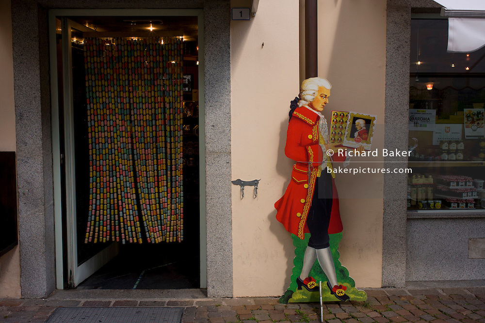 """Advertising 'Mozartkugeln' is a life-size cut-out of Austrian composer Wolfgang Amadeus Mozart outside a shop in the Italian border town of Brixen-Bressanone in South Tyrol but near the Austrian Brenner Pass. A Mozartkugel or 'Mozart ball' is a small, round confectionary made of marzipan, nougat and dark chocolate. It was originally known as the """"Mozartbonbon"""", and was created by Salzburg confectioner Paul Fürst in 1890."""