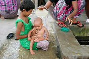 A woman washes her baby on the streets of Mandalay on 24th May 2016