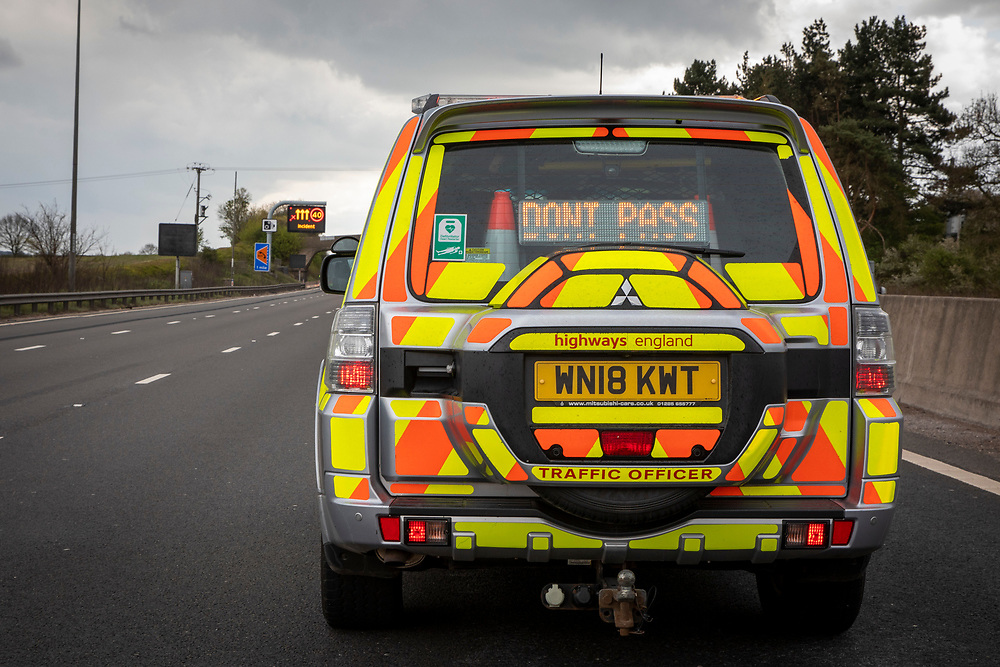 """A Highways England enforcement officer stops all traffic using a """"DO NOT PASS' sign on the south bound lane of the M1 motorway somewhere near Loughborough so that her colleagues can safely remove a broken down vehicle from the carriageway on the 29th of April 2021, United Kingdom. Highways officers patrol motorways to ease congestion and ensure the roads are safe and efficient for all users.  (photo by Andrew Aitchison / In pictures via Getty Images)"""