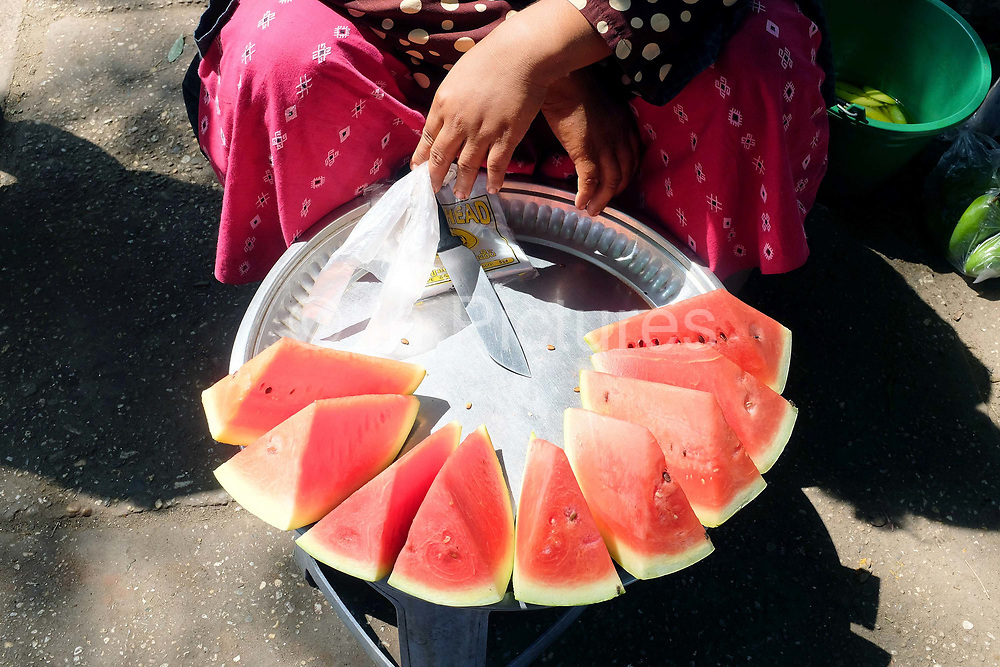 A woman selling locally grown watermelon on the platform at Danyingone Station on 19th March 2016 in Yangon, Myanmar.  Danyingone Station is one of the Circular Railways 39 stations.