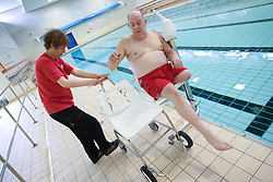 Disabled man; with the assistance of a member of staff; moving from chair of portable aquatic lift onto wheelchair at the swimming pool at his sports leisure centre,