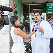 CAPTION: Dr González and his team work extremely hard to raise awareness throughout the nation. They try to make sure that any parent of a Honduran child born with a cleft, no matter where s/he lives in the country, knows they can come to Hospital Escuela for top quality cleft care from friendly and caring professionals. LOCATION: Hospital Escuela, Tegucigalpa, Honduras. INDIVIDUAL(S) PHOTOGRAPHED: Unknown (left) and Dr Luis González (right).