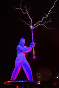 A dancer throwing live electric lightning bolts as part of the  the Arcadia robotic spider performance at Glastonbury Festival 25th July 2016, Somerset, United Kingdom.  The spider is both a dj booth playing rave tunes through the night and a piece of spectacular performance with electric dancers and fire blasts. The Glastonbury Festival runs over 3 days and has 3000 acts, including music, art and performance and approx. 150.000 attend the anual event.