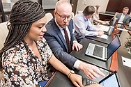 Coworkers collaborate on at the conference table during a meeting. A lifestyle portrait by Arkansas commercial photographer, Alex Kent.