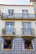 Neighbouring friends at the window of a ceramic tile-decorated facade at Madragoa district in Lisbon