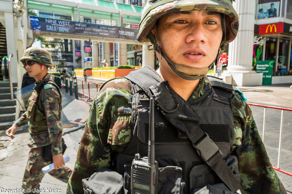 """01 JUNE 2014 - BANGKOK, THAILAND:  Thai soldiers patrol the Ratchaprasong district in Bangkok. The Thai army seized power in a coup that unseated a democratically elected government on May 22. Since then there have been sporadic protests against the coup. The protests Sunday were the largest in several days and seemed to be spontaneous """"flash mobs"""" that appeared at shopping centers in Bangkok and then broke up when soldiers arrived. Protest against the coup is illegal and the junta has threatened to arrest anyone who protests the coup. There was a massive security operation in Bangkok Sunday that shut down several shopping areas to prevent the protests but protestors went to malls that had no military presence.    PHOTO BY JACK KURTZ"""