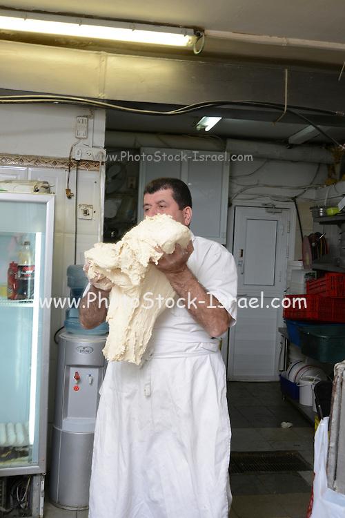 Pita Bakery. Baker is kneading the dough